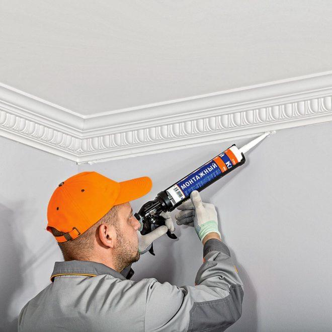 строитель клеет потолочный плинтус